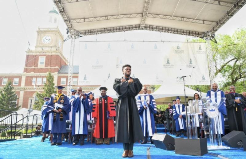 查德維克博斯曼(中)在2018年,受邀回母校霍華德大學畢業典禮致詞,擺出「瓦干達萬歲」的手勢。(翻攝自Howard University官方臉書)