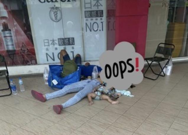 一家三口直接大字型躺在地板排口罩,還讓嬰兒與地板直接接觸引網炮轟。(圖片截自《高雄爆料公社》)