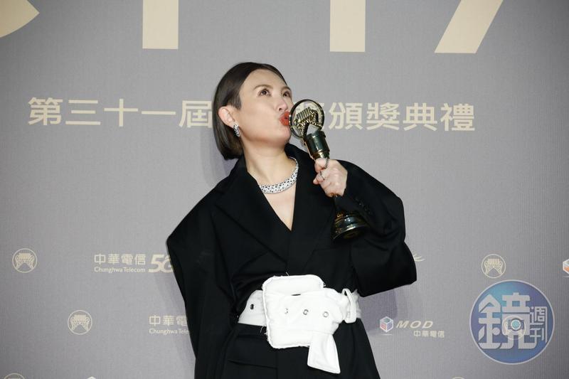 獲得最佳國語女歌手獎的魏如萱,在後台開心親吻獎座。