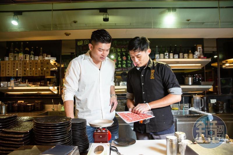 吳念忠(左)常巡視店面,確保肉的品質。