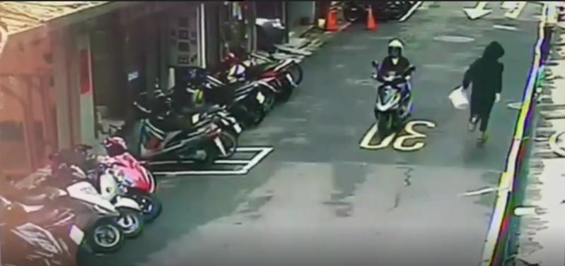 一名黑衣人持白色塑膠桶,朝港人餐廳潑雞屎後狂奔逃逸。(翻攝畫面)