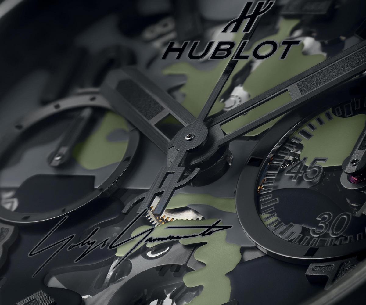透過藍寶石錶盤的疊加印刷設計讓迷彩面盤充滿層次感,同時面盤6點鐘還有山本耀司簽名字樣。