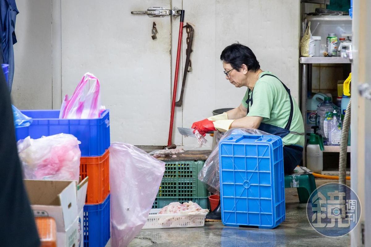 「朴子魚丸店」老闆在後頭蹲坐,費工刮著魚肉。