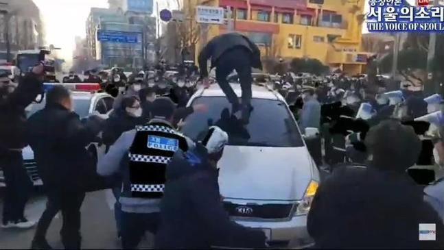 趙斗淳12日出獄,民眾跳上他乘坐的公務車洩憤。(翻攝The Voice of Seoul YouTube頻道)