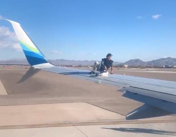 一名行為脫序的男子跳上飛機機翼,他在機翼中段坐了下來,還對機內乘客擺弄姿勢。(翻攝自推特@mickakers)