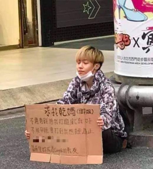 最近「阿姨,我不想努力了」成為網路流行語,一位金髮小正太在西門町舉牌「求找乾媽」。(翻攝自爆廢公社2館臉書)