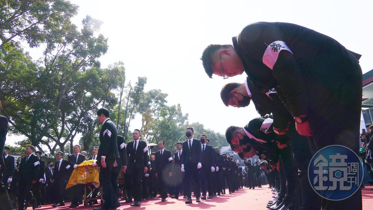 移靈時,手掛義字臂章的黑衣人像洪的棺木鞠躬。(讀者提供)