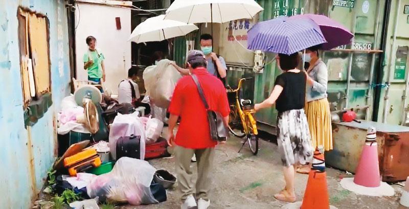 南港區公所協同各局處單位會勘後,協助住民將垃圾打包清出。(南港區公所提供)