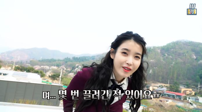IU到屋頂上拍MV,自曝曾被帶到屋頂上遭對方要錢。(翻攝自YouTube畫面)