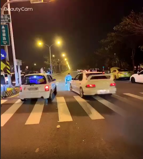 違法競速的車輛差點衝撞擔任裁判的藍衣男子。(翻攝畫面)