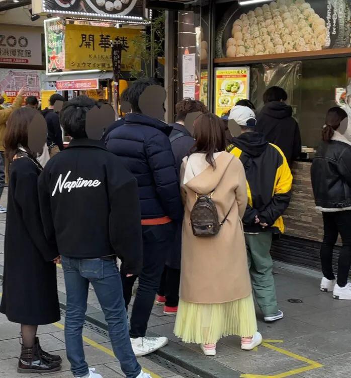 身穿駝色大衣的福原愛和A男在橫濱中華街約會,和其他情侶一樣排隊買包子。(翻攝自《女性SEVEN》)