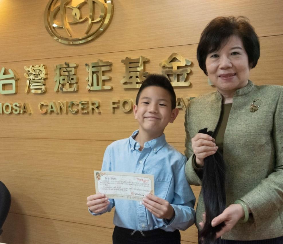 台灣癌症基金會副執行長蔡麗娟(右)接受敏睿(左)捐髮並頒贈感謝小卡。(台灣癌症基金會提供)