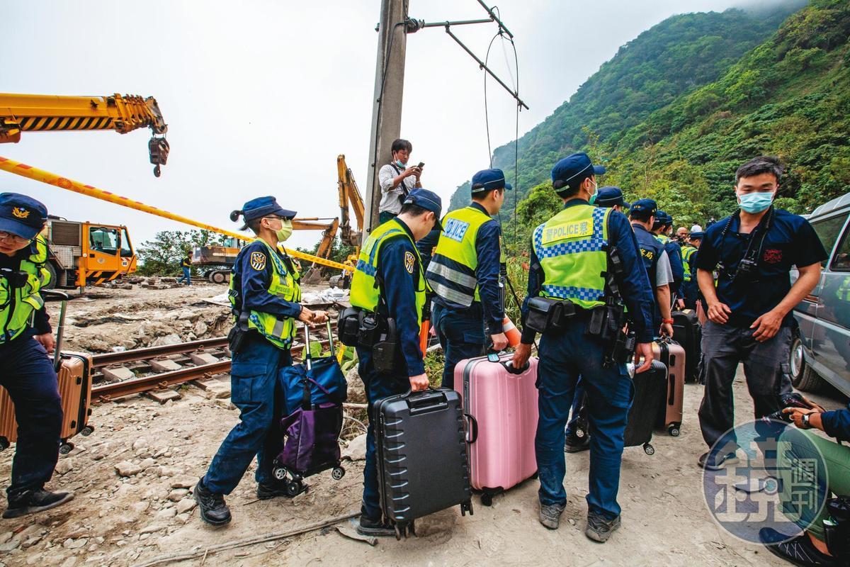 鐵路警察協助將乘客遺留在車廂內的行李箱搬出。