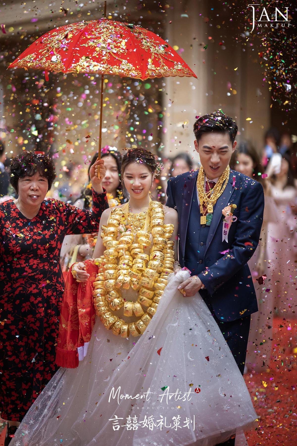新娘脖子上掛了3條由龍鳳手鐲做的金項鍊,仍挺直了背、抬起頸部,撐起驚人的重量。(翻攝JanMakeup微博)