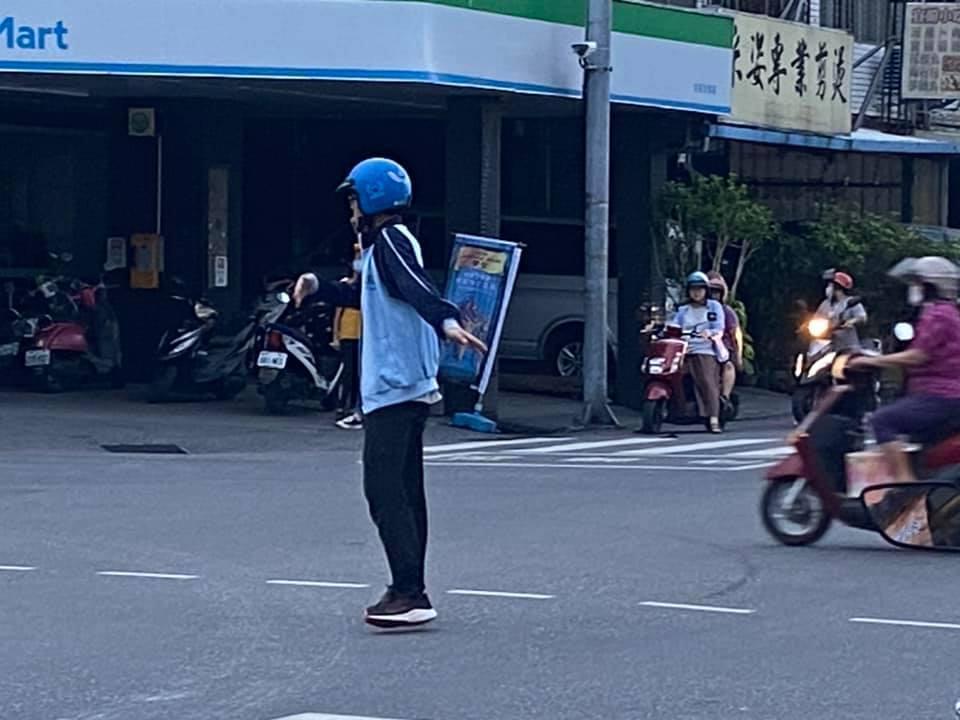 男學生頭戴安全帽,站在路口中央指揮車輛通行。(翻攝自花蓮同鄉會)