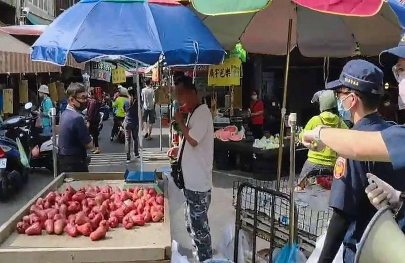 一名攤商將口罩拉到下巴被警方勸導,一度乖乖戴口罩但事後又將口罩拉下。(警方提供)